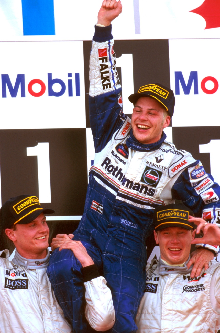 Jerez, Spain. 24-26 October 1997. Mika Hakkinen and David Coulthard (McLaren Mercedes) hold Jacques Villeneuve, the new World Champion aloft on the podium in celebration. Ref-97 EUR 16. World Copyright - LAT Photographic